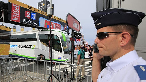 A French gendarme talks on his communication equipment while a man lets the air out of the tyre of the Orica GreenEDGE cycling team bus