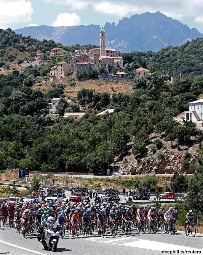 The pack of riders cycles on its way past the village of Soveria during the 156 km second stage of the centenary Tour de France cycling race from Bastia to Ajaccio