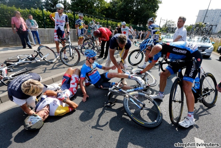 Riders lie on the road after crashing in the last 3km of the twelfth 218km stage of the centenary Tour de France cycling race from Fougeres to Tours