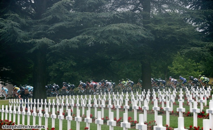 The pack of riders cycles past the cemetery outside of the WWI Douaumont ossuary near Verdun during the 234.5 km seventh stage of the Tour de France cycling race from Epernay to Nancy