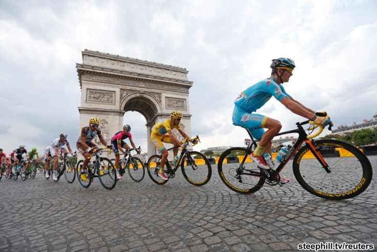 The pack of riders including race leader Astana team rider Vincenzo Nibali of Italy cycles near the Arc de Triomphe at the end of the final 21st stage of the Tour de France cycle race