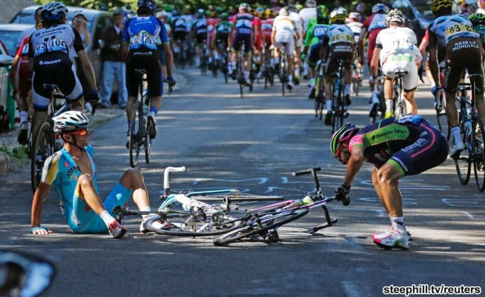Astana team rider Scarponi of Italy and Lampre-Merida team rider Rodolfo Serpa of Colombia recover after crashing during the 187.5-km 11th stage of the Tour de France cycling race between Besancon and Oyonna