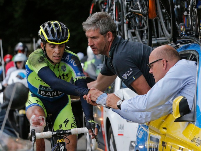 Spain's Alberto Contador gets assistance from his team after crashing during the tenth stage of the Tour de France cycling race over 161.5 kilometers (100.4 miles) with start in Mulhouse and finish in La Planche des Belles Filles, France, Monday, July 14, 2014. Contador withdrew from the race as a result of the crash, right is his team manager Bjarne Riis of Denmark. (AP Photo/Christophe Ena)