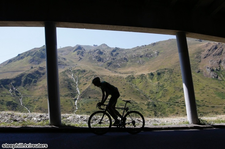 A silhouetted rider climbs during the 188-km (116.8 miles) 11th stage of the 102nd Tour de France cycling race from Pau to Cauterets in the French Pyrenees mountains, France, July 15, 2015.  REUTERS/Eric Gaillard - RTX1KE5K