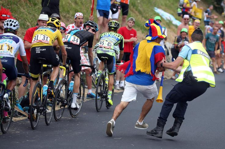 LA TOUSSUIRE, FRANCE - JULY 24:  A Columbian supporter is removed from the course by a Gendarmerie as the group of the yellow jersey with Nairo Quintana of Columbia riding for Movistar Team in the best young rider white jersey, Chris Froome of Great Britain riding for Team Sky in the overall race leader yellow jersey, Woeter Poels of the Netherlands riding for Team Sky and Rafal Majka of Poland riding for Tinkoff-Saxo race to the finish of stage 19 of the 2015 Tour de France from Saint-Jean-de-Maurienne to La Troussuire on July 24, 2015 in La Toussuire, France.  (Photo by Doug Pensinger/Getty Images)